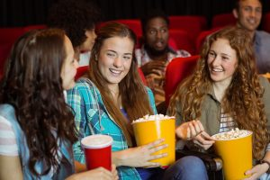 Young friends watching a film at the cinema and enjoying popcorn