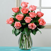 productThis arrangement of 12 pink roses in a glass vase is classy, minimal and perfect for those who have an elegant taste. Hand gathered fresh long stem pink roses are arranged in a clear glass vase. Green leaves harmoniously heighten the gracious look of the pink roses. Sprinkle some water droplets and the sweet smelling roses are ready to be gifted. This arrangement makes for a perfect professional or personal gift.