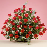 productThis gorgeous basket of 50 red roses is sure to have a mesmerizing effect on whoever sees it. As vivacious as a fresh rose plant, this bouquet is arranged with fresh leaves, fillers and ferns that add to the volume and beauty of the arrangement. The fresh rose flowers spread the sweetest fragrance. The cane basket almost gets hidden with the spread of the long stem roses and fillers, adding to the look. Easy to carry and display on tabletops, this one is a preferred choice for almost all occasions.