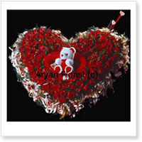 Heart Shaped Arrangement Of 100 Red Roses With a Teddy Bear Placed In The Center Of The Arrangement