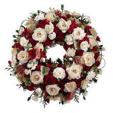 productThis wreath is created with beautiful blooms of various kinds. Fresh and handpicked, they are delicately placed to form a pleasant and lovely testament to the circle of life. Evoking fond memories and goodness of the deceased, this arrangement is a lovely offering.