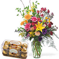 Pink Roses, Orange Gerberas And Yellow Lilies with Some Ferns In Glass Vase Along with A Box of 16 Pcs Ferrero Rocher