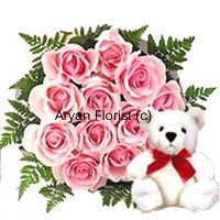 A dozen pink roses have been bundled up to create this pretty bouquet that comes with a cute little teddy bear. The 12 roses are delicately handpicked and bundled into a round bouquet surrounded by green leaves and ferns. Order it for friends or your special loved one for any occasion. The white teddy bear wears a red bow delivering cuteness with sweet smelling pink roses.