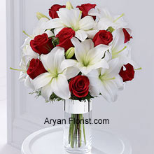 productThe combination of red roses with white Oriental lilies is a surreal one, that is indeed a harbinger of Christ! So, let's welcome the season of festivities, mirth, joy, and happiness with this lovely arrangement of flowers put together in a crystal clear cylindrical vase that is wrapped in silver ribbon to elevate the feeling of these magical days. (Please Note That We Reserve the Right to Substitute any Product with a Suitable Product of Equal Value in Case of Non-Availability of a Certain Product)