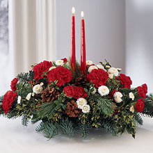 A soothing combination of red carnations and white Gerberas are apt for this season of merrymaking. The two red taper candles add to the charm of this arrangement that can be used as a centerpiece. The red signifies warmth and love, whereas the white embodies the feeling of peace and tranquility, each balancing the extremity of the other. This is the true spirit of Christmas as love is the central theme of the festival. (Please Note That We Reserve the Right to Substitute any Product with a Suitable Product of Equal Value in Case of Non-Availability of a Certain Product)